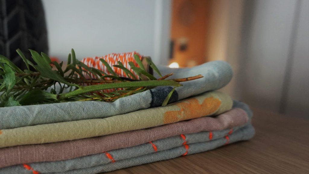 Ein Stapel bunter Stoffe mit verschiedenen Mustern. Blumen und buntes Garn zur Dekoration.