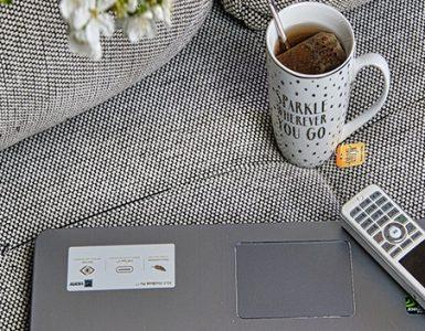 Eine Tasse Kaffe, ein Laptop und ein Telefon auf einem Sofa