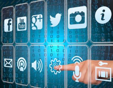 Ein großer Finger, welcher Verschiebene Symbole anwählt welche für Digitalisierung stehen sollen. Unter anderem Logos von Sozialen Netzwerken(Facebook, YouTube, Instagram etc.)